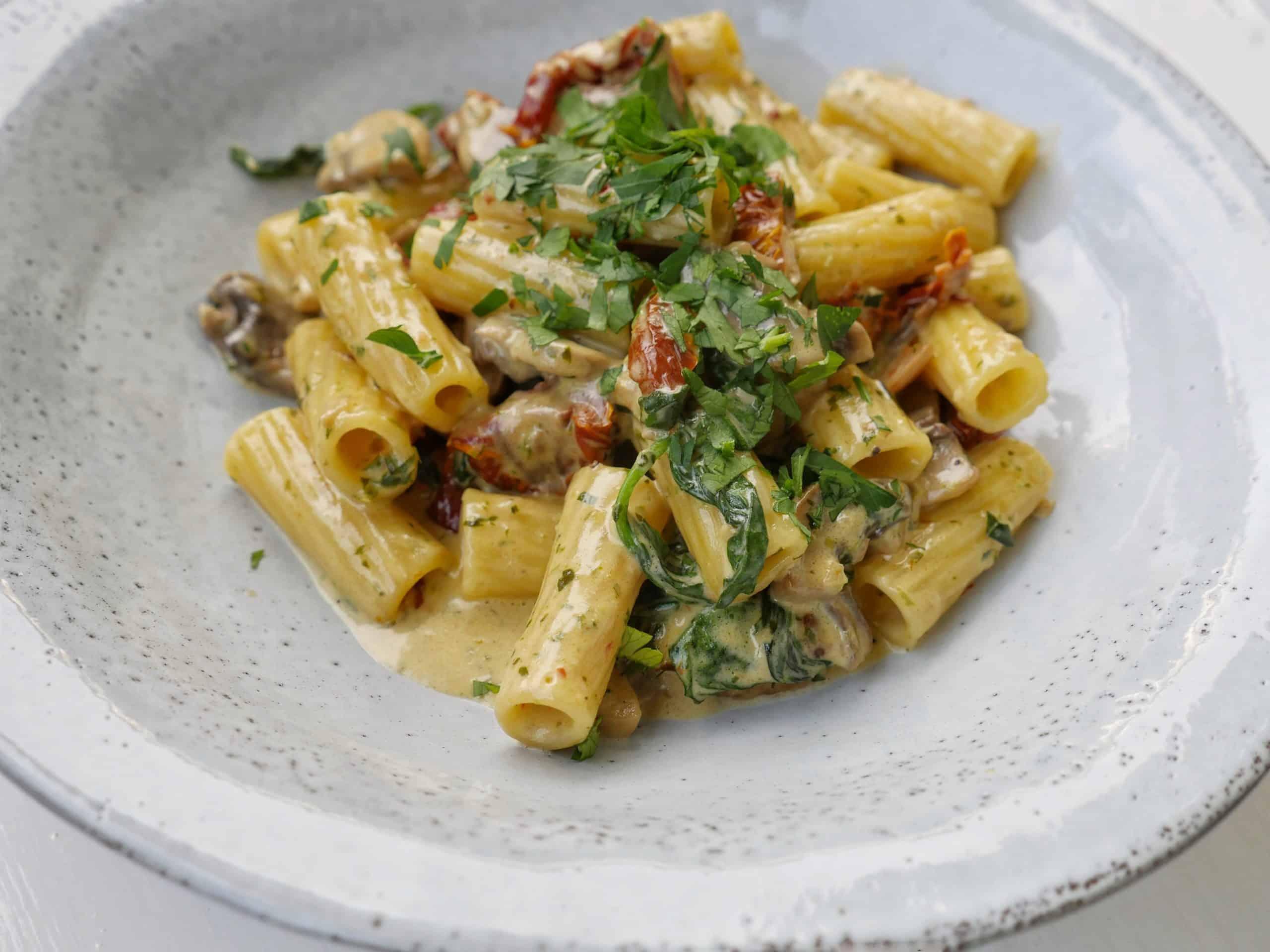 Vegetarisk pasta med champinjoner, soltorkade tomater, pesto och spenat
