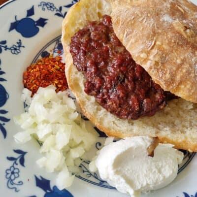 Pljeskavice med pitabröd, chilflakes, lök och kajmak